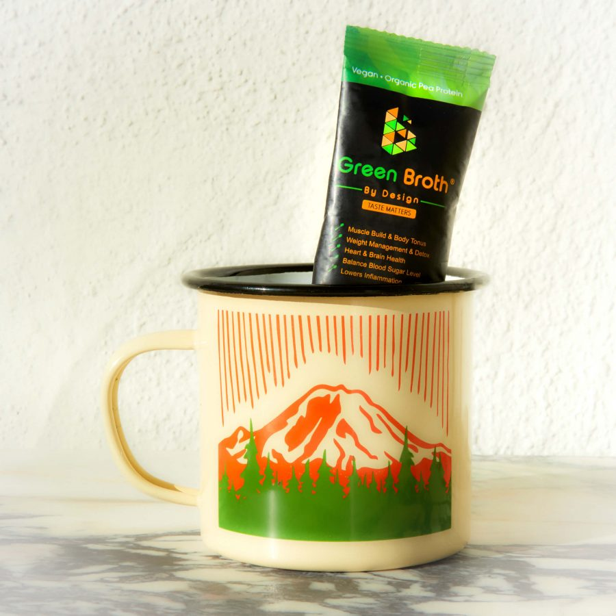 Green broth sachet in a cup with mountains