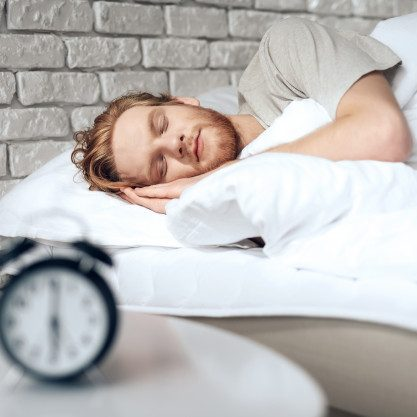 red haired young man sleeps bedroom near alarm clock
