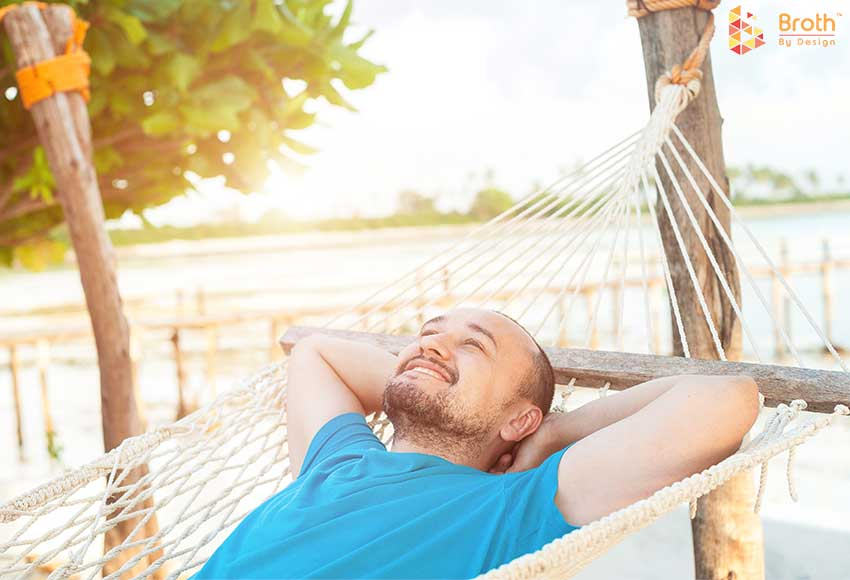 A person relaxing on a hammock in the summer.